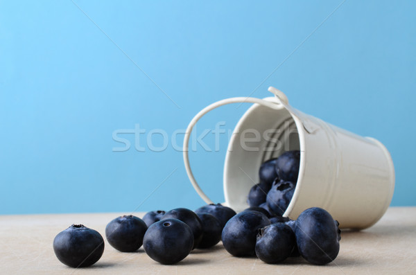 Bucket of Blueberries Spilling on to Wooden Table with Light Blu Stock photo © frannyanne