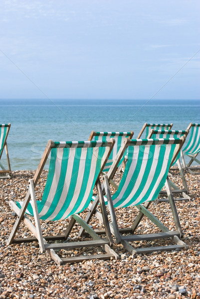 Striped Deckchairs on Pebbled Beach Stock photo © frannyanne