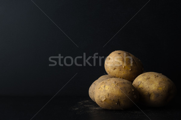 Whole, Unpeeled Potatos on Black with Soil Stock photo © frannyanne