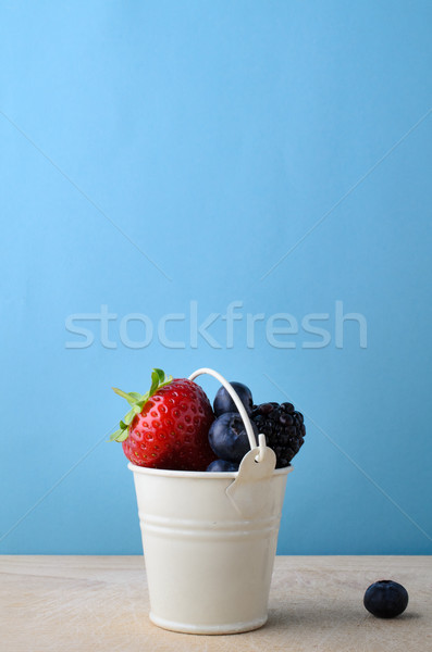 Enamel Bucket Filled with Fresh Fruit Berries on Wood with Blue  Stock photo © frannyanne