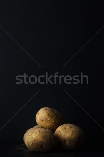 Potatoes Grouped with Soil on Black Slate Stock photo © frannyanne