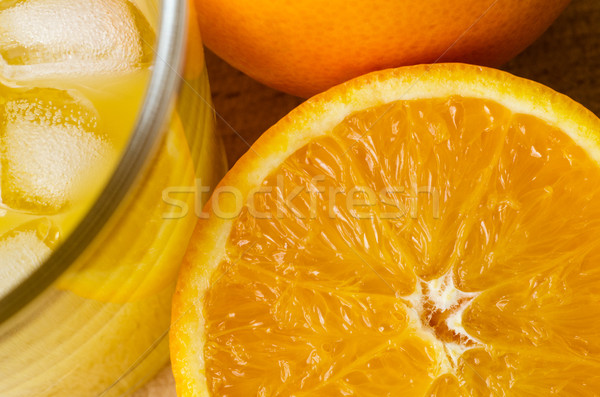 Freshly Cut Orange with Glass of Juice and Ice Cubes on Wood Stock photo © frannyanne