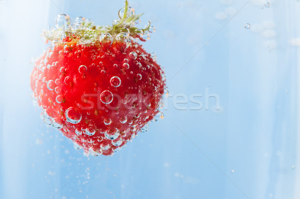 Red Strawberry Floating in Bubbles of Sparkling Blue Water Stock photo © frannyanne