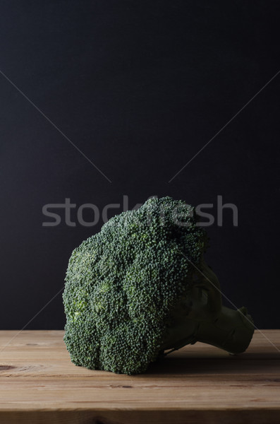 Head of Dark Green Broccoli on Wood Plank Table against Black Ba Stock photo © frannyanne