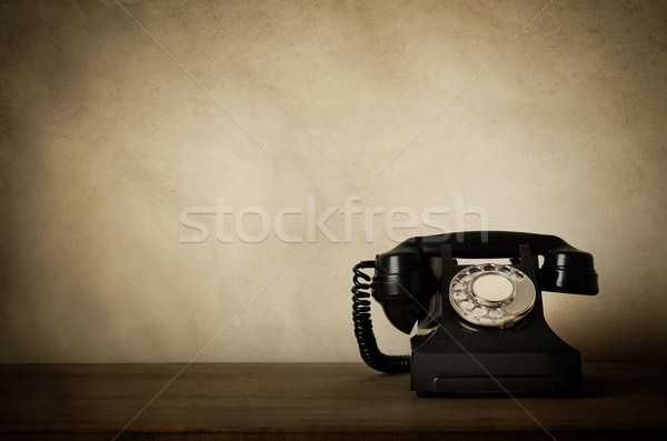Vintage Black Telephone with Aged Effects on Wooden Desk Stock photo © frannyanne