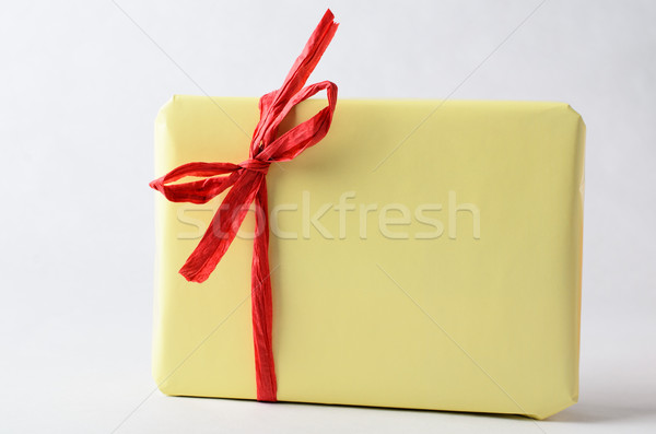 Simple Gift Package in Yellow with Red Raffia Ribbon Stock photo © frannyanne