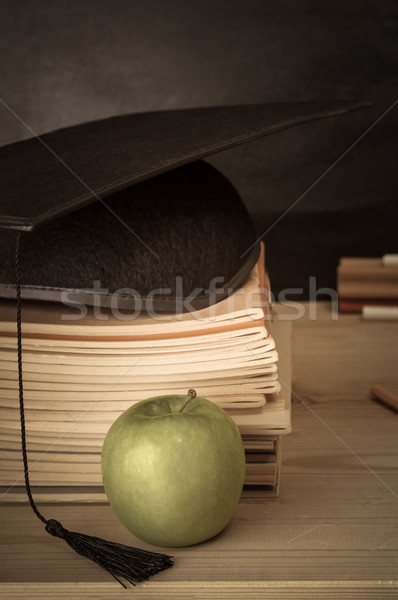 Teachers Desk with  Books Stacked, Mortarboard, Apple and Chalkb Stock photo © frannyanne