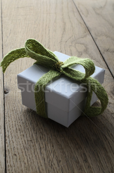 White Gift Box with Soft Green Ribbon on Old Wood Table Stock photo © frannyanne