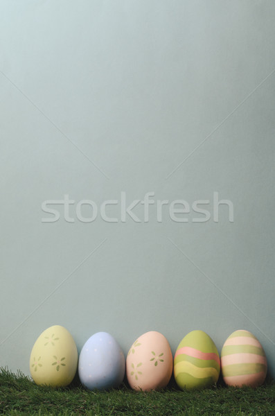 Row of Decorated Easter Eggs on Grass with Blue Background Stock photo © frannyanne