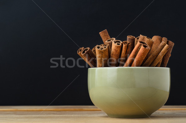 Green Bowl of Cinnamon Sticks on Wood with Black Background Stock photo © frannyanne