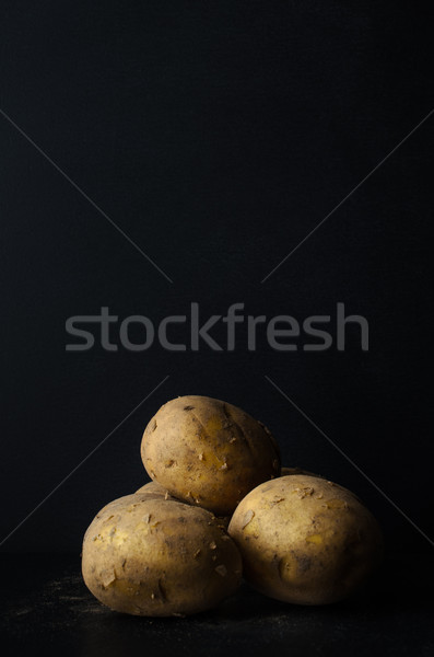 Potatoes Still Life on Black Slate with Soil Dusting Stock photo © frannyanne