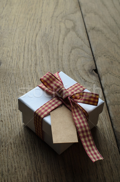 Stock photo: Single Gift Box with Gingham Ribbon and Blank Label on Wood