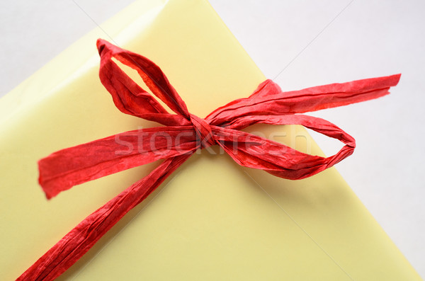Red Raffia Bow on Yellow Gift Wrapped Package Stock photo © frannyanne