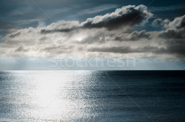 Shimmering Light on Sea with Moody Dark Sky Stock photo © frannyanne