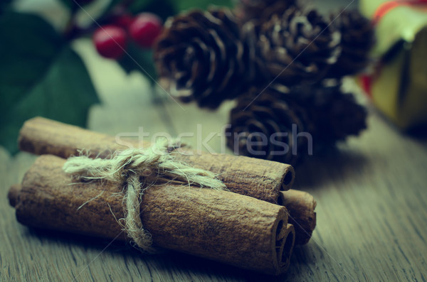 Stock photo: Cinnamon Sticks Bundle, Holly and Fir Cones on Oak Table - Retro