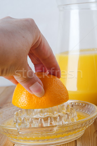 Hand Squeezing Orange on Manual Glass Fruit Juice Extractor Stock photo © frannyanne