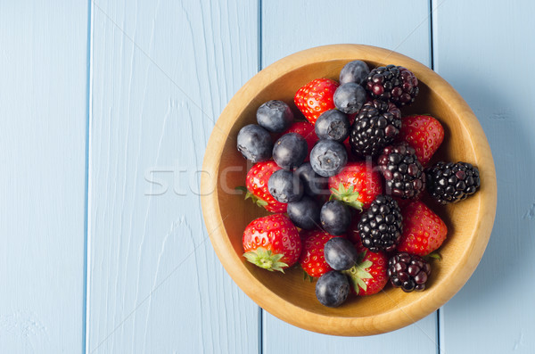 Mixed Berry Fruits in Wooden Bowl on Light Blue Wood Planked Tab Stock photo © frannyanne