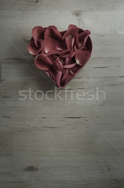 Plum Toned Rose Petals in Heart Shaped Bowl on Wood Stock photo © frannyanne
