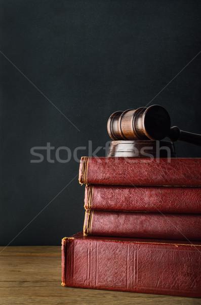 Wooden Gavel Topping Old Book Stack on Oak Desk with Blackboard  Stock photo © frannyanne