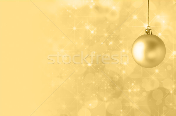 Yellow Christmas Bauble on Starry Bokeh Background Stock photo © frannyanne