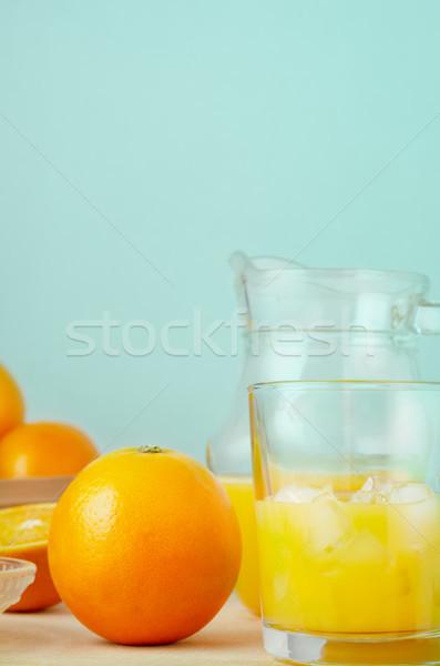 Freshly Squeezed Orange Juice on Wood Table with Aqua Background Stock photo © frannyanne