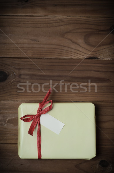 Wrapped Gift Package with Red Raffia Bow on Wood Planking - Retr Stock photo © frannyanne