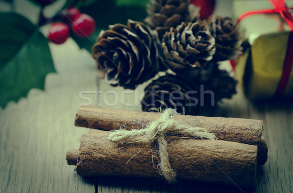 Cinnamon Sticks Bundle, Holly and Fir Cones on Oak Planked Table Stock photo © frannyanne