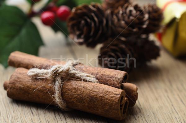 Cinnamon Sticks Bundle, Holly and Fir Cones on Oak Table Stock photo © frannyanne