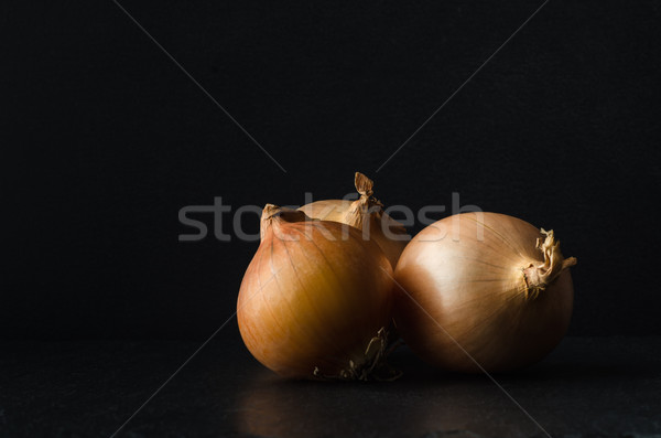 Group of Three Onions on Black  Slate Stock photo © frannyanne