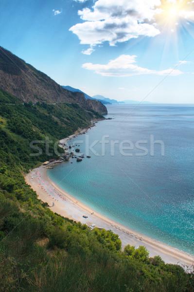 Homokos tengerpart hegyek tenger égbolt víz tájkép Stock fotó © frescomovie