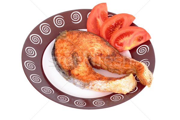 Salmon steak with vegetables on plate. Isolated on black Stock photo © frescomovie