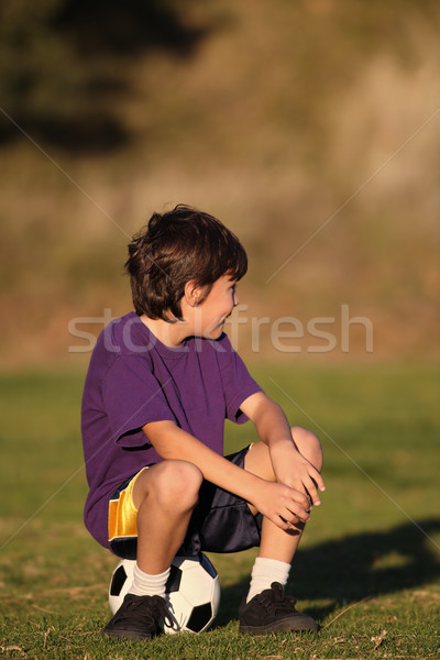 Garçon séance ballon regarder côté fin Photo stock © Freshdmedia
