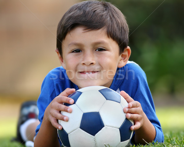 Jeunes hispanique garçon couché ballon brun Photo stock © Freshdmedia