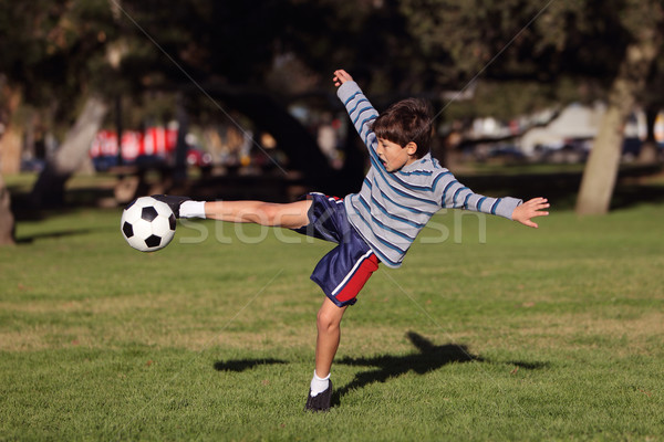 Young boy playing with soccer ball in the park Stock photo © Freshdmedia