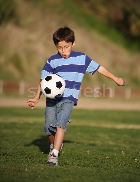 Latino boy playing with soccer ball Stock photo © Freshdmedia