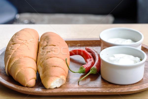 Fehér kenyér tejföl piros bors fából készült tányér Stock fotó © frimufilms