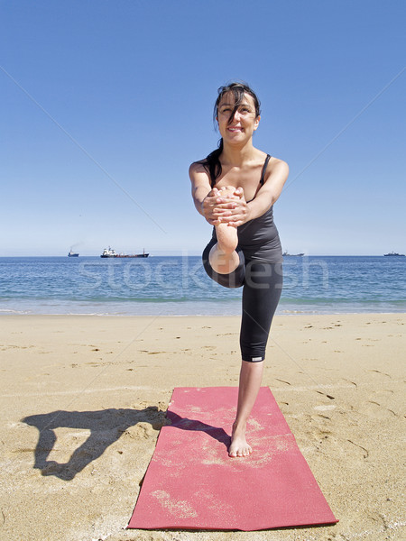 Bikram yoga dandayamana janushirasana frontal pose at beach Stock photo © fxegs