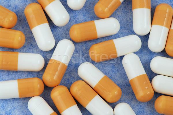 Capsules jaune blanche médicaux isolé bleu Photo stock © fyletto