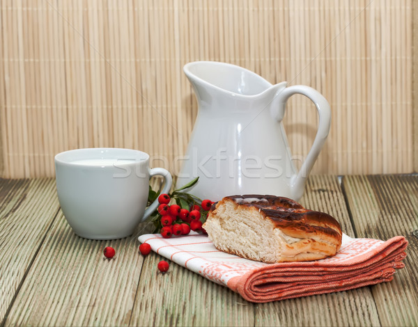 pitcher of milk and a piece of cake on a wooden table Stock photo © g215