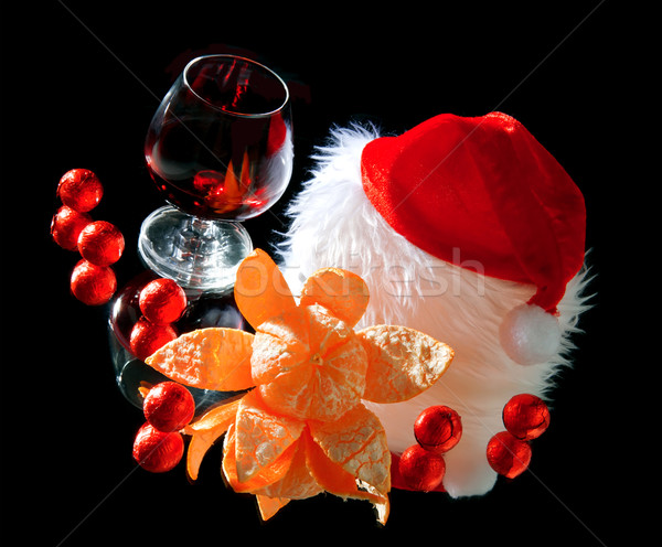 Glasses of wine, tangerine and chocolate and Santa Claus hat on a black background Stock photo © g215