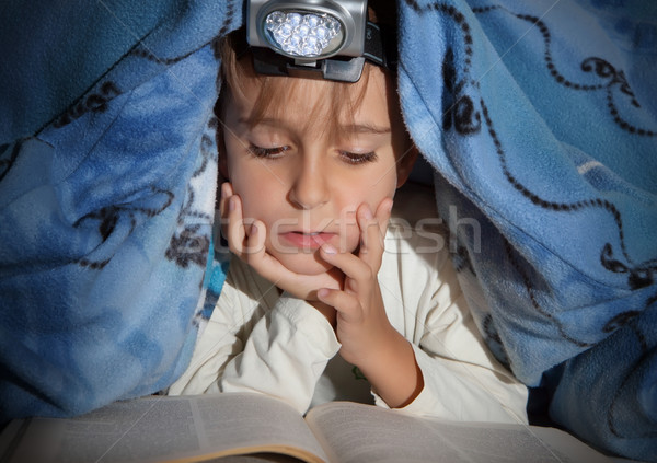 Boy reading a book under the covers with a flashlight  Stock photo © g215