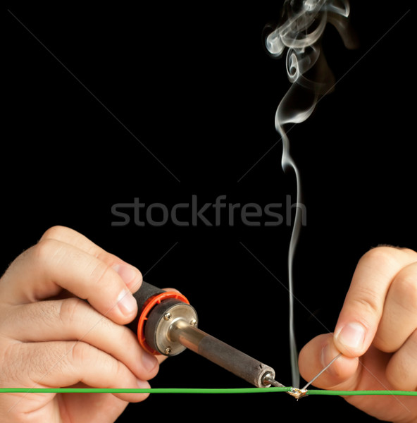 Stock photo: Technician soldering two wires together on a black background.