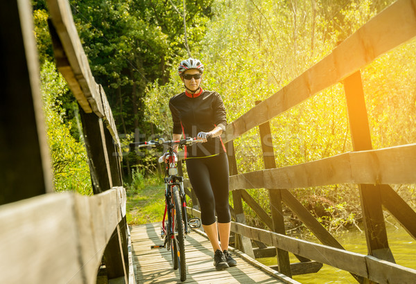 Young woman riding a bicycle in a bridge at sunset. Stock photo © gabor_galovtsik