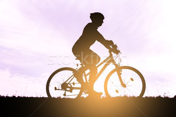 Silhouette of the cyclist at dawn. Stock photo © gabor_galovtsik
