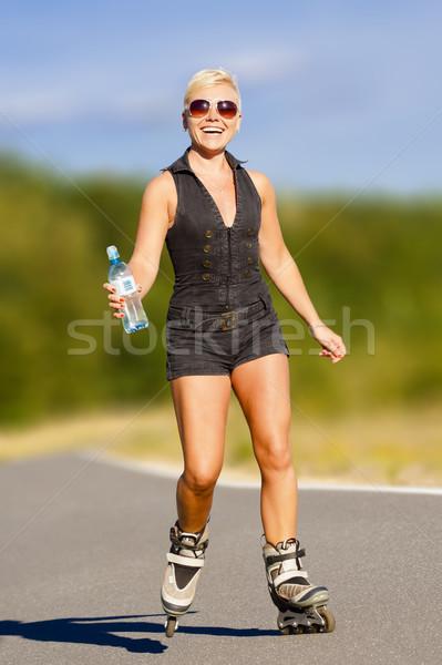 Jeunes femme de remise en forme femme blonde eau boire bouteille Photo stock © Gbuglok