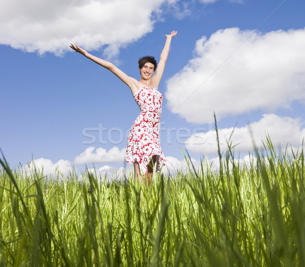 Young woman standing on a field with her arms raised Stock photo © gemenacom