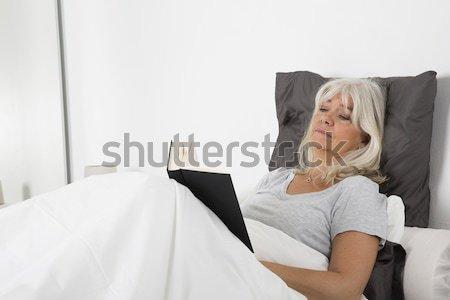 Genç kız kitap bakıyor kamera yatak bakmak Stok fotoğraf © gemenacom