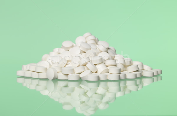 Stack of pills towards green background Stock photo © gemenacom