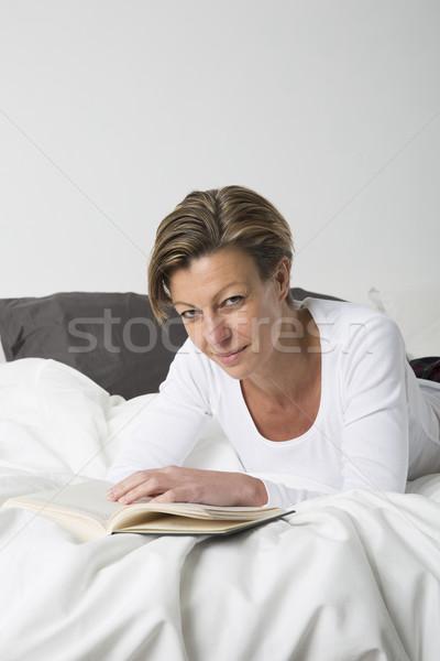 Femme souriante lecture livre lit cheveux courts femmes Photo stock © gemenacom