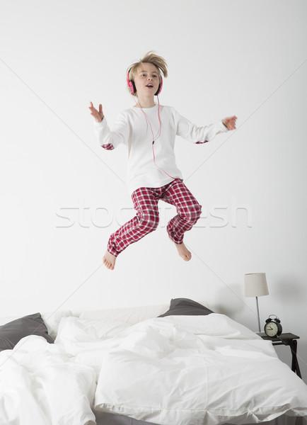 女の子 ヘッドホン ジャンプ ベッド 幸せ 音楽 ストックフォト © gemenacom